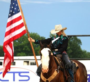 cowgirl on horse holding the american flag.