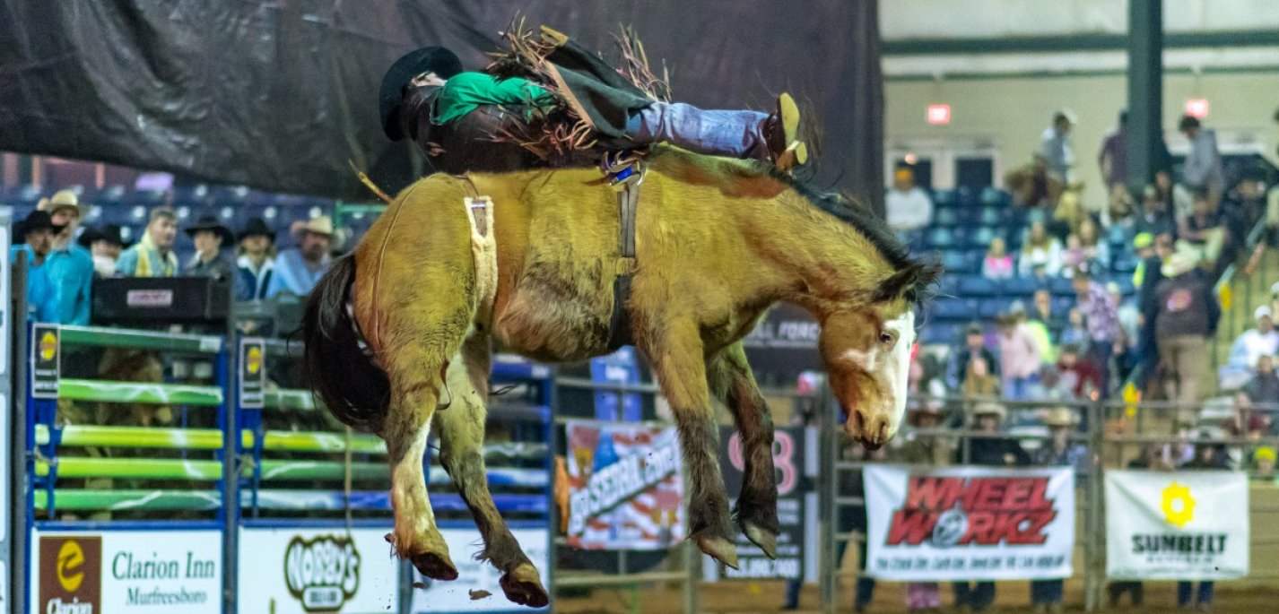a cowboy on a horse jumping in the air